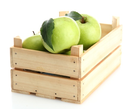 Ripe green apples with leaves in wooden crate isolated on white photo