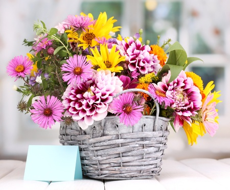beautiful bouquet of bright flowers in basket on wooden table photo
