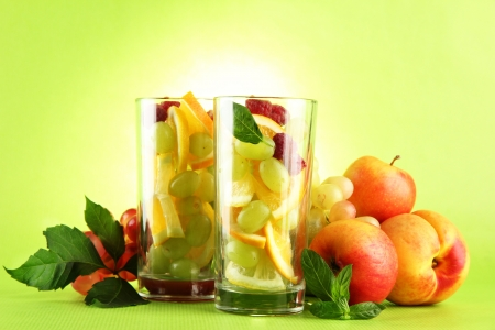 transparent glasses with citrus fruits, on grren background Stock Photo - 16620414