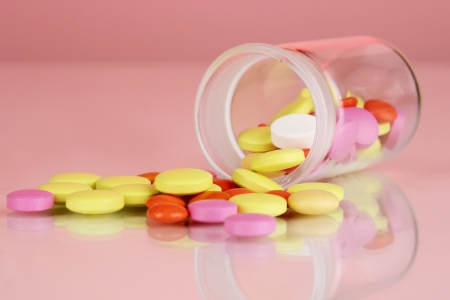 Pills in receptacle on red background Stock Photo - 16620520