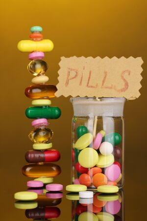 Capsules and pills hill and in receptacle on yellow background photo