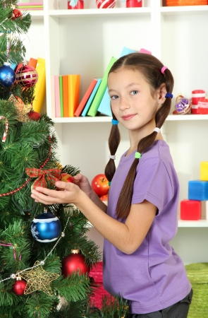 Little girl decorating christmas tree photo