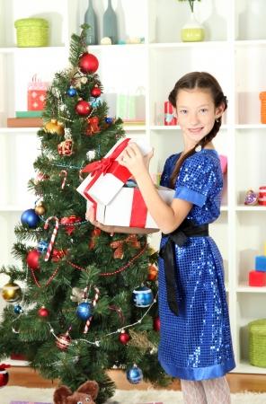 Little girl holding gift box near christmas tree Stock Photo - 17129855
