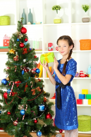 Little girl holding gift box near christmas tree Stock Photo - 17129867