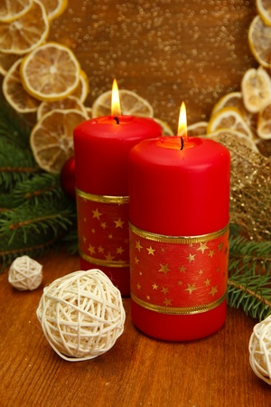 Two candles and christmas decorations, on golden background photo