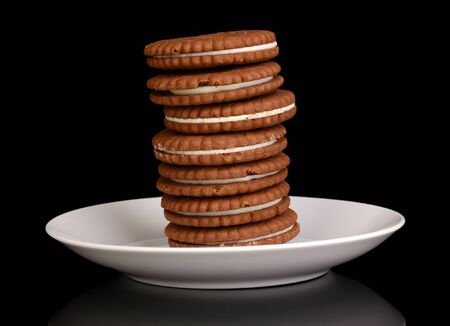 nutritiously: Chocolate cookies with creamy layer on plate isolated on black