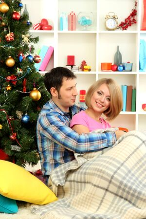 Young happy couple near a Christmas tree at home photo