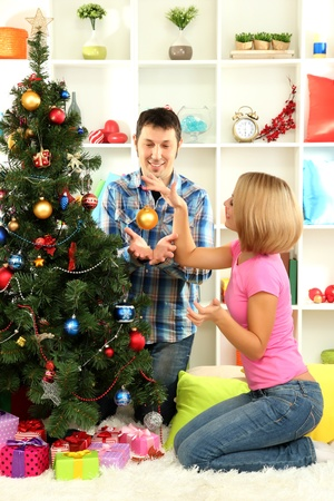 Young happy couple  decorates Christmas tree at home photo