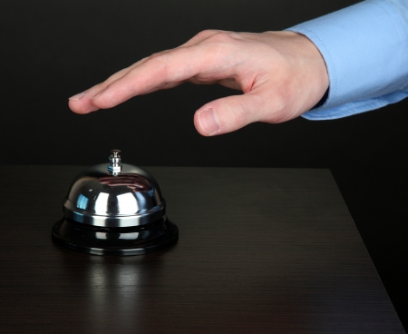 reception counter: Hand ringing in service bell on wooden table on black background
