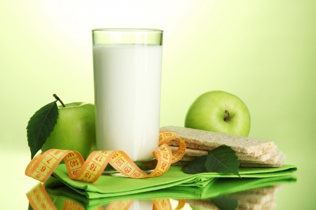 Glass of kefir, apples, crispbreads and measuring tape, on green background Stock Photo - 16669500