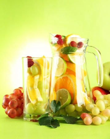 jar and glass with citrus fruits and raspberries, on green background photo