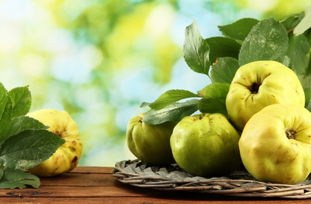 sweet quinces with leaves, on wooden table, on green background photo