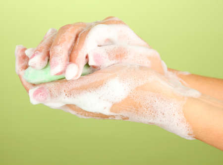 soapsuds: Womans hands in soapsuds, on green background close-up