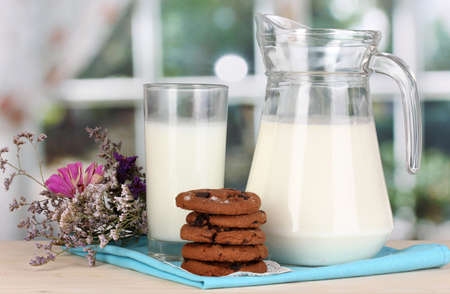 Pitcher and glass of milk with cookies on wooden table on window background photo