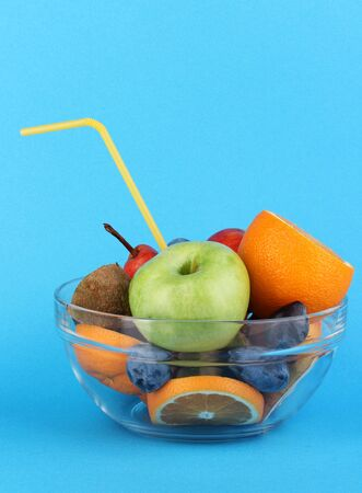 Glass bowl with fruit for diet on blue background Stock Photo - 16670097