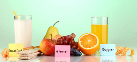Dietary foods for breakfast, dinner and supper on green background photo