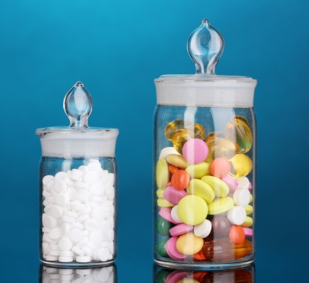 Capsules and pills in receptacles on blue background Stock Photo - 16669370
