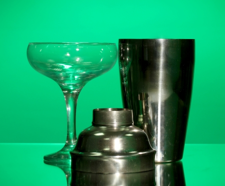 Cocktail shaker and cocktail glass on color background photo