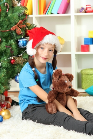 Little girl  sitting near christmas tree Stock Photo - 17129894