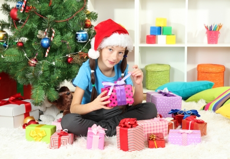 Little girl holding gift box near christmas tree Stock Photo - 17129892