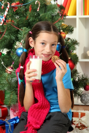 Little girl with pink scarf and glass of milk sitting near christmas tree Stock Photo - 17129895