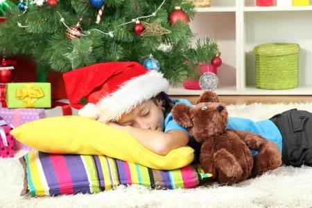 Little girl sleeping near christmas tree Stock Photo - 17129893