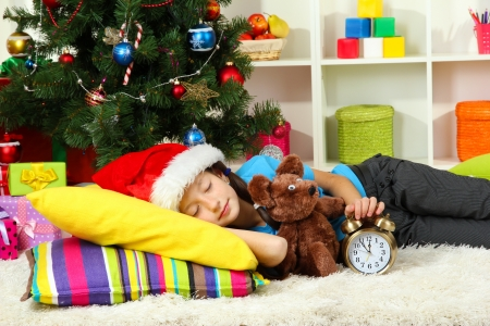 Little girl sleeping near christmas tree photo