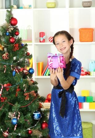 Little girl holding gift box near christmas tree Stock Photo - 17129882