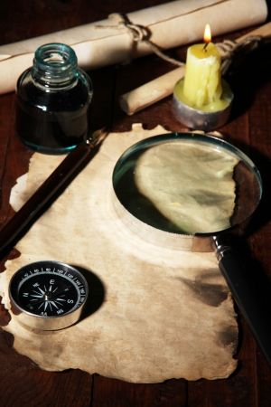 Old paper with ink pen and magnifying glass near lighting candle on wooden table Stock Photo - 16670302