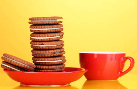 Chocolate cookies with creamy layer on red plate yellow background Stock Photo - 16669545