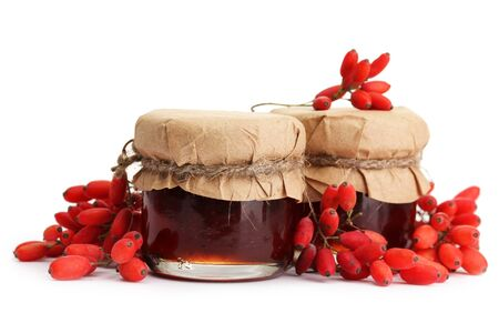 ripe barberries and jars of jam isolated white photo