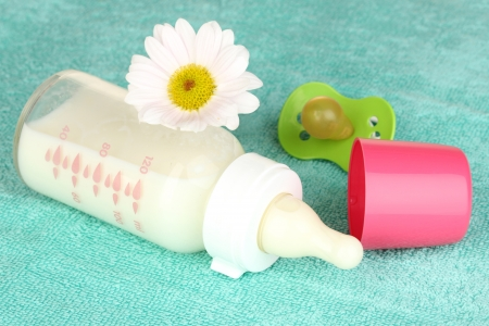 Baby bottle of milk on blue towel photo