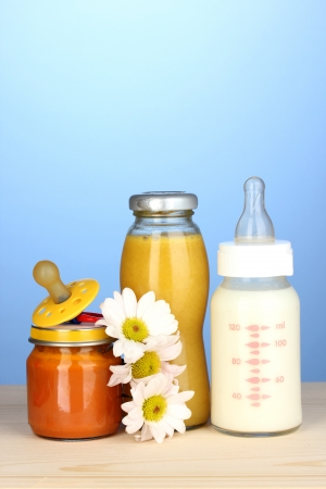 teat: Baby food, bottle of milk, puree and juice on blue background