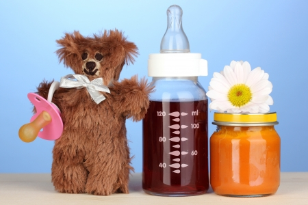 Baby bottle with fresh juice, puree and teddy bear on blue background photo