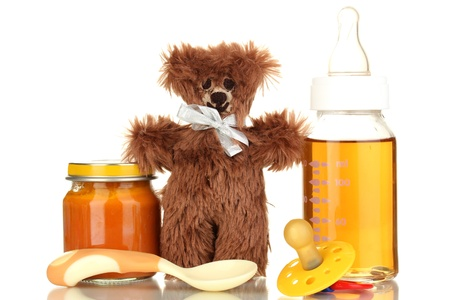 nursing bottle: Baby bottle with fresh juice, puree and teddy bear isolated on white