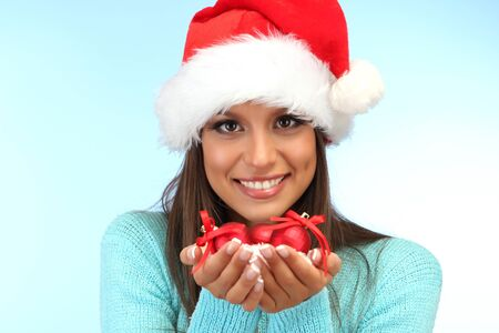 beautiful young woman holding snow with christmas balls, on blue background photo