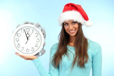 beautiful young woman with clock, on blue background Stock Photo - 17132570