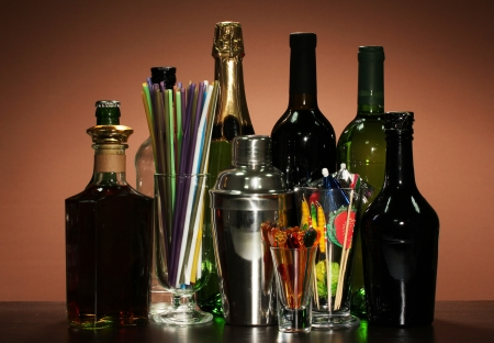 Collection of drinks, cocktail shaker and  other bartender equipment on color background photo