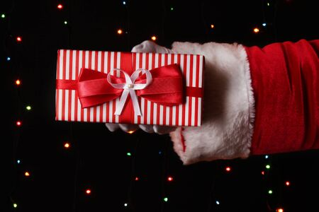 Santa Claus hand holding gift box on bright background Stock Photo - 16728195