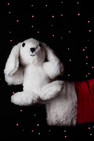 Santa Claus hand holding toy rabbit on bright background Stock Photo - 16728330