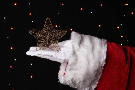 Santa Claus hand holding christmas star on bright background Stock Photo - 16728176
