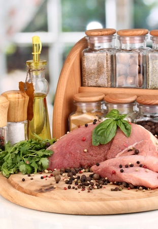 microelements: A large piece of pork marinated with herbs, spices and cooking oil on board on white table on window background Stock Photo