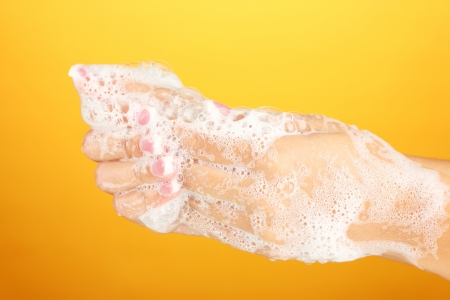 soapsuds: Womans hands in soapsuds, on orange background close-up Stock Photo