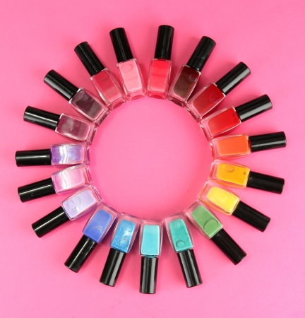varnish: Group of bright nail polishes, on pink background Stock Photo