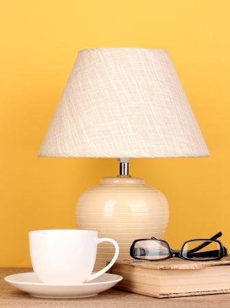 table lamp with cup, book and glasses on yellow background photo