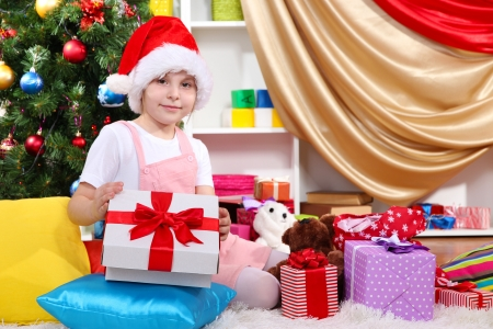 A little girl opens a gift in festively decorated room photo