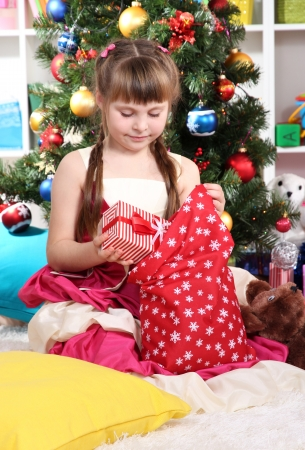 gets: A little girl gets gifts from bag of Santa Claus in festively decorated room Stock Photo