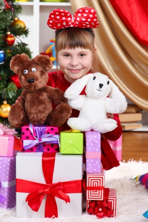 festively: Beautiful little girl in red dress surrounded by gifts and toys in festively decorated room