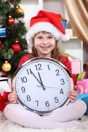 przewidywanie: PiÄ™kna dziewczynka z zegarem w oczekiwaniu na Nowy Rok w Å›wiÄ…tecznie pokoju