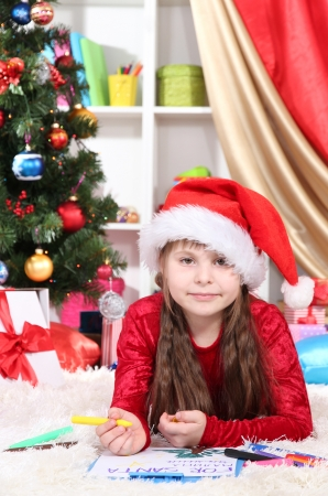 festively: Beautiful little girl writes letter to Santa Claus in festively decorated room Stock Photo